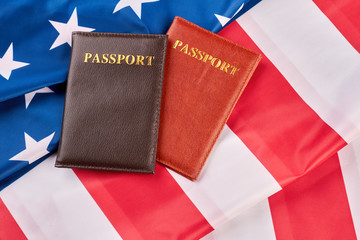 Close up two passports on American flag. Personal documents on USA flag background, horizontal image. Citizenship of America.