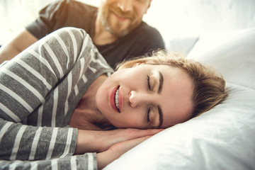 Portrait of tranquil smiling woman sleeping on white pillow. Caring partner is lying behind and looking at her with love