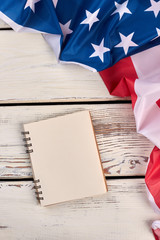USA flag and blank paper notebook. United States flag and notepad on vintage wooden background, top view.