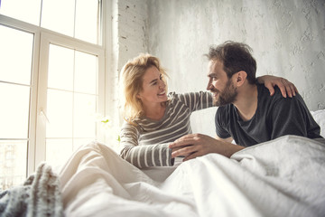 Happy two smiling people who are in love. They are meeting morning together sitting in bed and showing fondness to each other. Lady is putting arm around partner neck and looking at him with love
