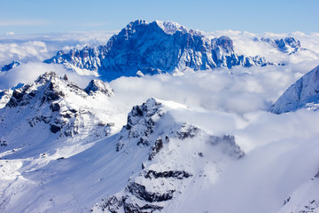 Stunning sunny winter view to peaks in moutains and clouds, Dolomites Alps Italy