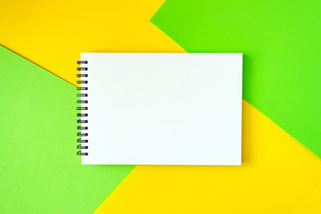 Minimal, pop art, abstract, vivid mockup with white notepad on bright green and yellow background.  Top view of open spiral blank notebook on a table. Flat lay