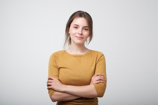 Portrait of young caucasian woman in yellow shirt casually standing near gray wall. Concept of being confident woman