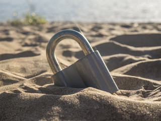 close up metal padlock on the sea coast in sand