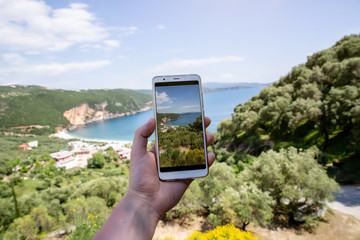Close-up photo of man's hand taking photo with modern smartphone. Sea coast