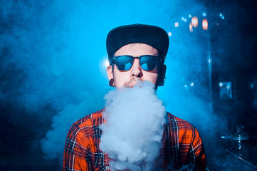 Punk hipster man in the vape shop is sitting at the bar and smoking a mechanical vape device. Toned image.