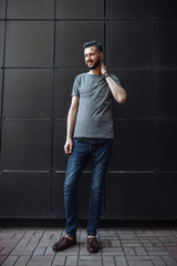 Photo of a cute stylish guy, a hipster in a gray empty t-shirt, standing in front of a black wall. Empty space for logo or design.