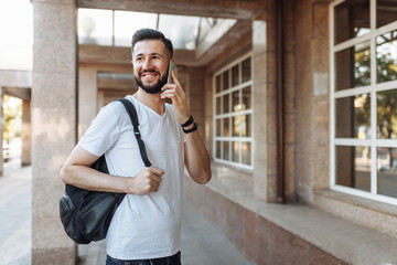Portrait of a beautiful stylish Guy talking on the phone, on the background of a glass building, can be used for advertising, text insertion