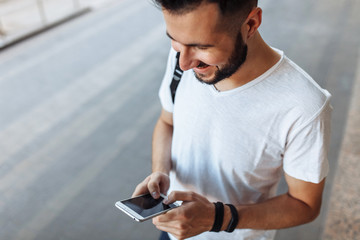 Portrait of a beautiful stylish guy looking at the phone, on the street against the building background, can be used for advertising, text insertion