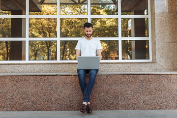Portrait of a beautiful stylish guy dressed in a white t-shirt, who sits on a parapet, works with a laptop, on the street against a glass building, can be used for advertising, text insertion