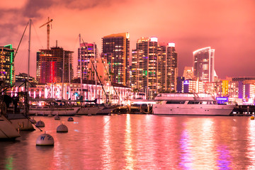 Wall Mural - Beautiful San Diego California at night after sunset with pink sky, skyline buildings, boats and water.
