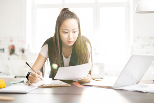 Portrait of focused creative Asian woman drawing sketches for while standing at work table in sunlit fashion design atelier, lens flare