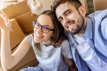 Content loving man and woman sitting among boxes and taking selfie with key of new apartment.