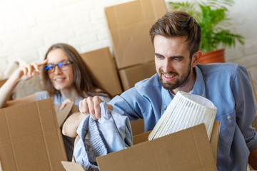 Smiling man looking inside of carton box while unpacking things on new place of living with girl.