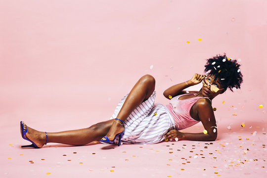 Portrait of a beautiful young woman lying on the floor with golden sunglasses, isolated on a studio background