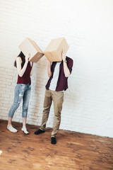 Casual man and woman with boxes on heads standing together in new empty apartment having fun