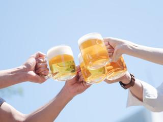 青空の下でビールで乾杯する男女4人の手元