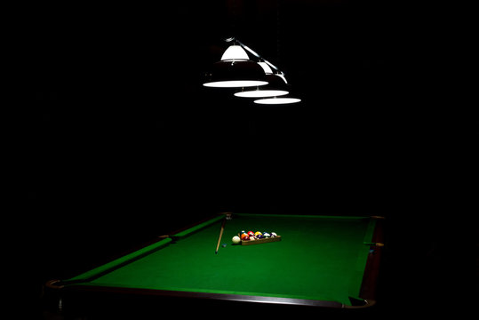 Game of billiards on a table with green cloth