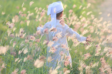 In the meadow there is a Muslim boy running with happiness