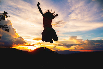 Silhouettes of happy little girl play jumping on mountain at sunset time