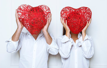 People hiding faces behind red heart.  St. Valentine's