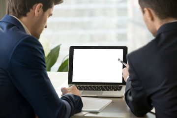 Two men in suits looking at mock up blank empty laptop screen in office. Copy space for business advertisement, commercial, product placement, corporate website. Close up focus on computer screen.