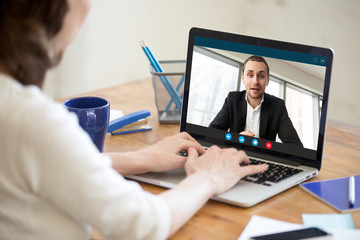Businesswoman making video call to business partner using laptop. Close-up rear view of young woman having discussion with corporate client. Remote job interview, consultation, online meeting concept.