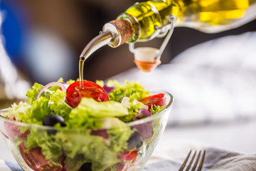 Olive oil pouring in to bowl of fresh vegetable salad