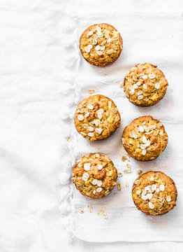 Whole grain mini muffins with dried apricots, oatmeal, apple, carrots and nuts on light background, top view. Copy space