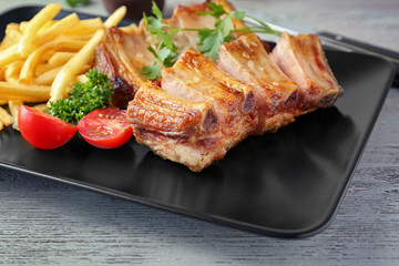 Aluminium Prints Pizzeria Plate with delicious grilled ribs and french fries on table