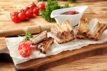 Wall Mural - Wooden board with delicious grilled ribs on table