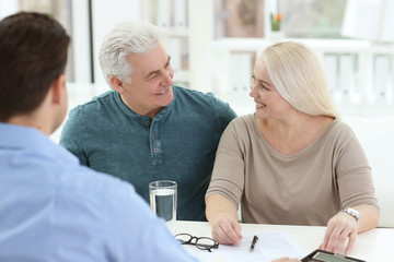 Mature couple discussing pension with consultant in office