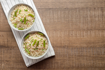 Bowls with brown rice and green beans on table