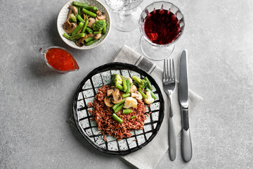 Plate with delicious brown rice and vegetables on table