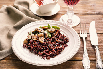 Plate with delicious brown rice, mushrooms and green beans on table