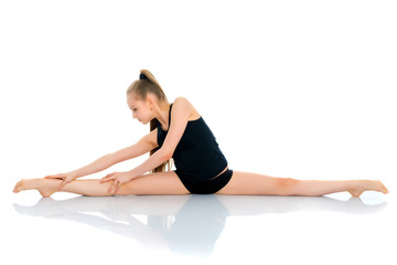 Girl gymnast perform the twine exercise.