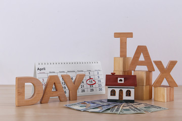 Phrase TAX DAY, wooden cubes, house model, calendar and money on table