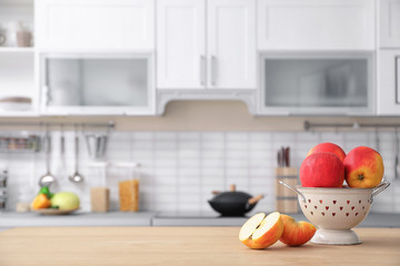 Ripe apples and blurred view of kitchen interior on background