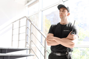 Male security guard with portable radio transmitter indoors