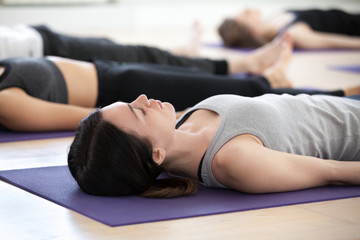 Yogi woman and a group of young sporty people practicing yoga lesson, doing Dead Body, Savasana pose, Corpse exercise, working out, indoor close up, students training in sport club