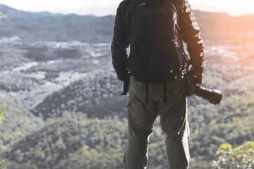 Nature photographer take photos with mirror camera on peak of mountain.