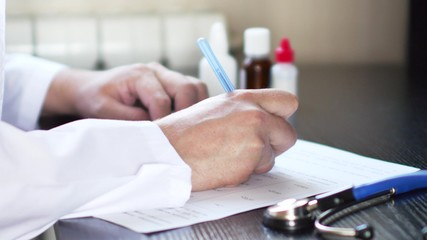 Male physician medicine doctor or pharmacist sitting at worktable and writing prescription on special form.