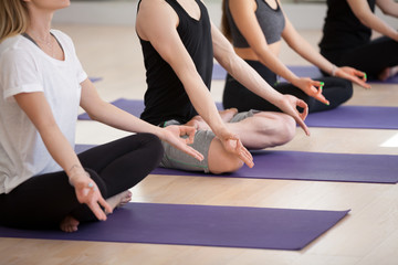 Group of young sporty people practicing yoga lesson, doing Sukhasana exercise, Easy Seat pose, working out, indoor close up, students training in sport club, studio. Wellness, wellbeing concept