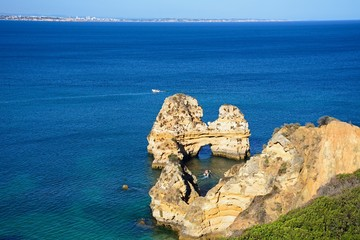 Elevated view of the coastline and a natural arch in the ocean and a boat to the centre, Praia da Dona Ana, Lagos, Portugal.