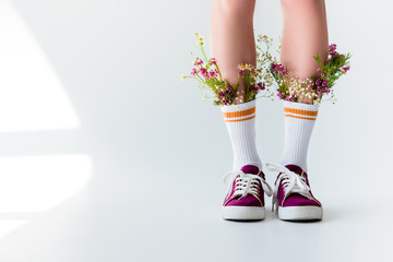 cropped shot of girl with fresh flowers in socks on grey