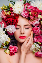 beautiful young woman with closed eyes posing in floral wreath isolated on grey
