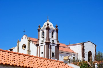 View of the Gothic cathedral (Igreja da Misericordia) and bell tower seen over rooftops, Silves, Portugal.