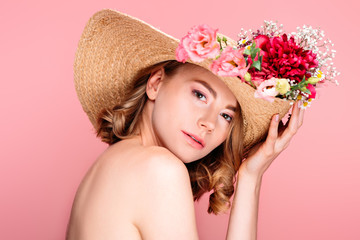 beautiful naked girl in hat with flowers looking at camera isolated on pink