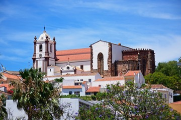 View of the Gothic cathedral (Igreja da Misericordia) and bell tower seen over town rooftops, Silves, Portugal.