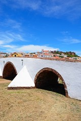 View of the Roman bridge across the river Arade with the Gothic cathedral, castle and town buildings to the rear, Silves, Portugal.